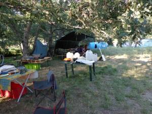 Le coin de préparation des repas, le coin vaisselle, et quelques chefs préparant des activités à l'ombre de l'abri-réfectoire des louveteaux.